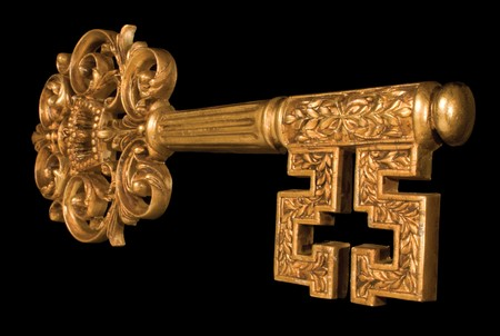 Ornate gold key at an angle on black