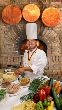 Gourmet chef preparing food in front of a brick country oven                               photo