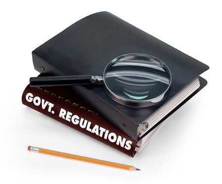 government regulations, magnifier, pencil Stock Photo