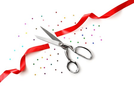Grand Opening illustrated with a scissors, a red ribbon and confetti on a white background