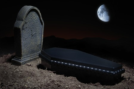 Grave site at night time with casket, headstone and moon in the sky photo