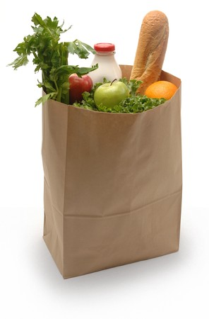 Brown paper bag filled with groceries on a white background photo