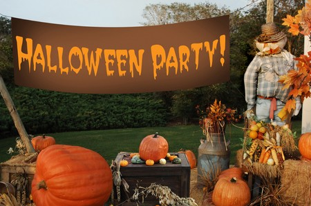 lawn party: autumn scene with pumpkins, scarecrow and banner that says Happy Halloween