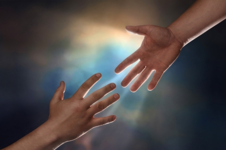 Two male hands; one reaching down to assist another hand reaching up with sunburst in the background photo