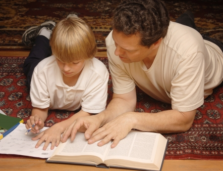 Parent helping child with homework Stock Photo