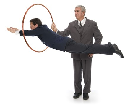 jump suit: CEO holding up a hoop for his employee  client  vendor to jump through Stock Photo