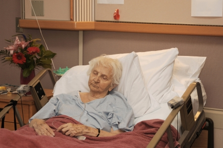 death and dying: Elderly woman in hospice bed Stock Photo