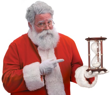 Santa on a white background pointing to an hour glass indicating that Christmas is fast approaching
