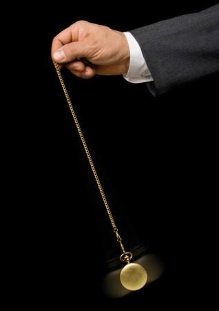 mans watch: Mano del hombre sosteniendo un reloj de bolsillo y el intercambio de pareja en la moda de un hipnotizador sobre un fondo negro  Foto de archivo