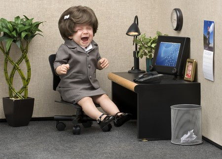 Baby dressed in professional office attire crying at her desk