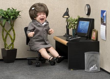 Bebé vestido con atuendo de oficina profesional llorando en su escritorio