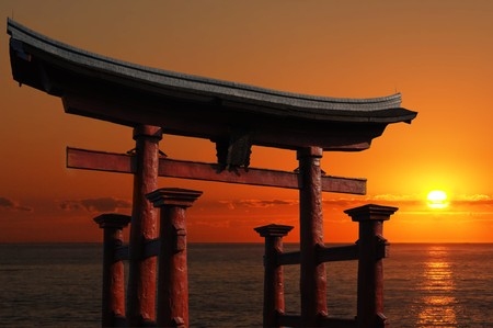 japanese temple: Japanese Temple Gate to Miyajima Shrine looking out over the ocean against a blazing red sunset