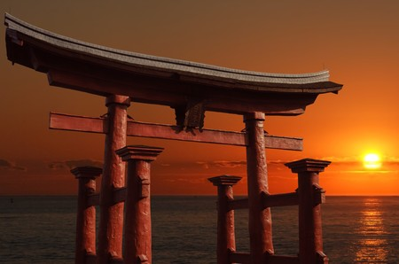 torii: Traditional floating Japanese gate at the entry to a Shinto shrine called a torii with a red setting sun in the background Editorial