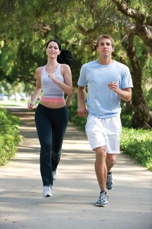 ジョグ: 魅力的な若いカップル、公園でジョギング