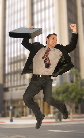 Happy businessman jumping in the middle of an urban street photo