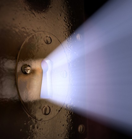A close-up of light pouring out of a key hole. photo