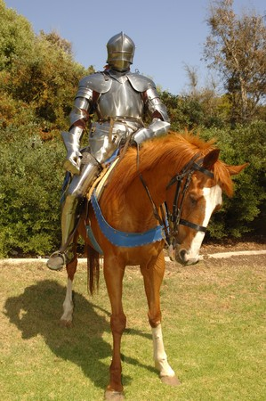 15th century knight in shining armour on horseback photo