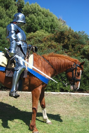 15th century English knight in full armour holding a sword on horseback