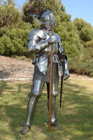 mediaeval: 15th Century English knight in shining armour standing outside with battle axe