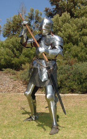 Knight in shining armour standing in attack position with a battle axe