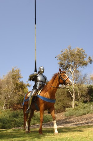 15th century: vertical full shot of 15th century knight in shining armour holding lance on horseback