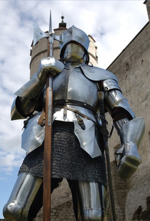 Worms eye view of a knight standing in front of a mediaeval castle photo