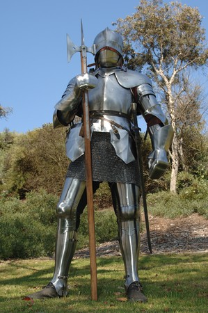 15th century English knight in full armour standing with battle axe shot from the front with a worms eye view