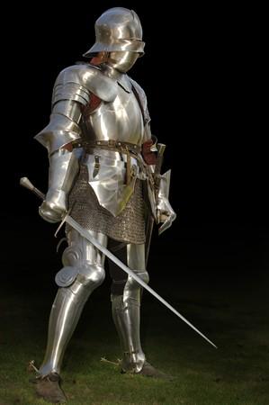 rycerz: Średniowieczne rycerz w shining armour XV wieku stałego poza Miecz. Samodzielnie na ciemnym tle