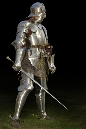15th century: Medieval knight in shining armour of the 15th century standing outside with sword. Isolated on a dark background  Stock Photo