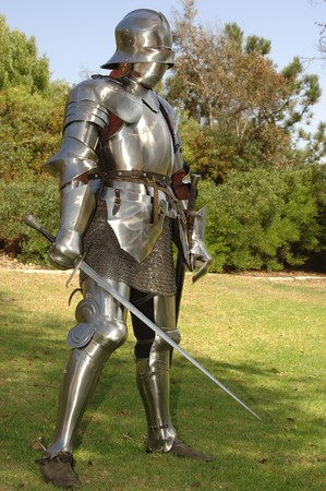 Mediaeval knight in shining armour of the 15th century standing outside with sword