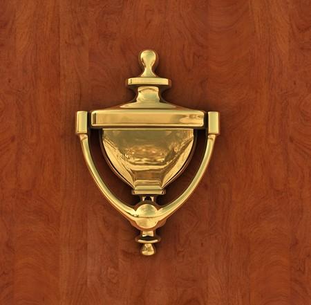 knocker: Classic brass door knocker on a wood background