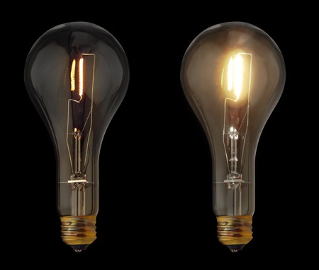 Two ideas represented as one dim light bulb and one bright light bulb isolated on black Reklamní fotografie
