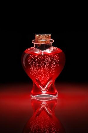 elixir: Botella de poci�n de amor en forma de un coraz�n lleno de l�quido de burbujeo rojo  Foto de archivo