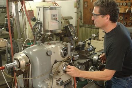 Maquinista trabajando un torno de metal Foto de archivo