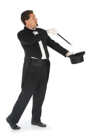 Mago profesional vistiendo esmoquin realizar sobre un fondo blanco