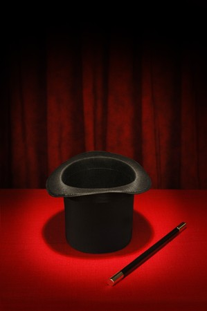 Magician's top hat and magic wand in spotlight on red table cloth and red draped background Stock Photo - 7053851