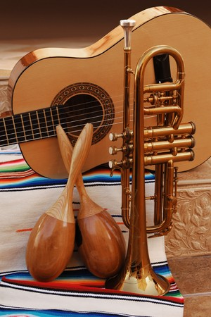accoustic guitar, maracas and trumpet on mexican fabric photo