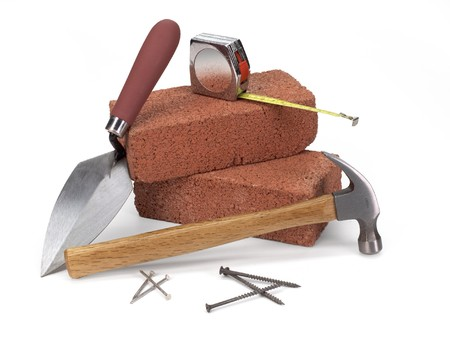 bricks, trowel, hammer & measuring tape on white