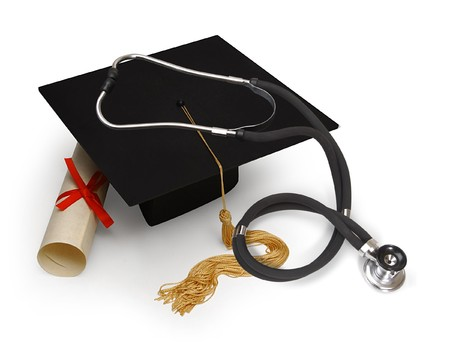 lak�hely: mortar board, diploma and stethoscope on white