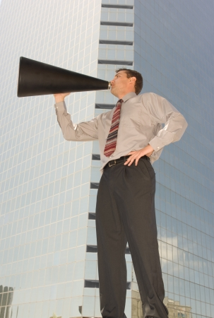Worms eye view of a businessman holding a megaphone with a skyscraper in the background