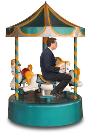going nowhere: Businessman sitting on a small merry-g0-round ride on a white background