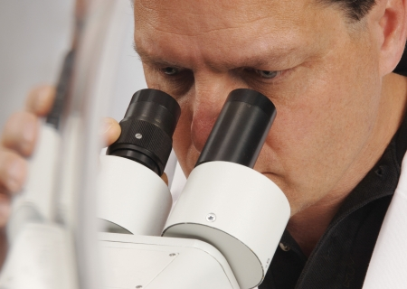pathology: Closeup of a man looking into a microscope