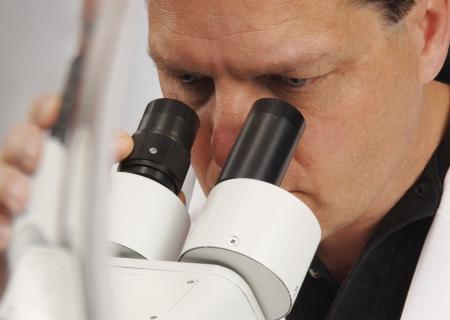 Detalle de un hombre en un microscopio