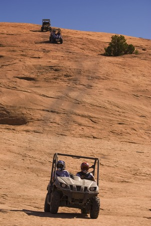 3 side-by-side ATVs coming down the side of a rock decline.  版權商用圖片
