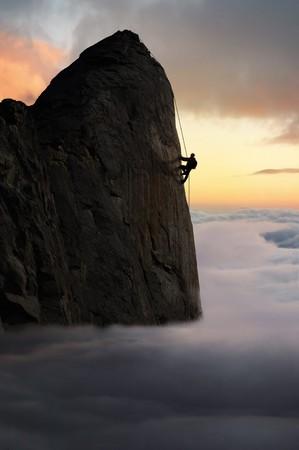 mountain climber: Profilo di un alpinista che raggiunge il picco di un volto di roccia sopra la base della nube Archivio Fotografico