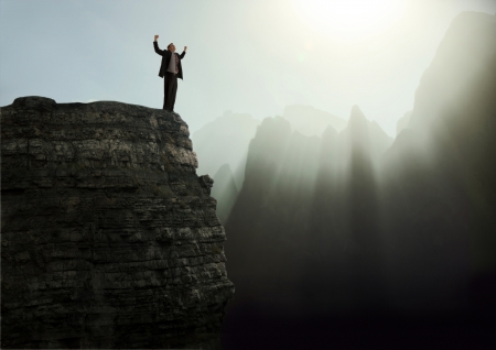 elation: Businessman standing with arms raised in elation on the top of a mountain peak