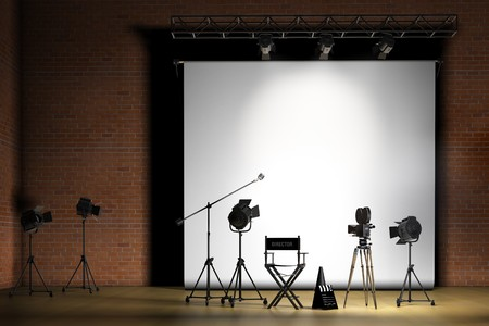 board: Movie set inside a sound stage with movie lights, movie camera, boom mic, directors chair, megaphone and clapper board Stock Photo