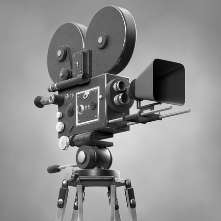 An old-fashoned movie camera on a tripod isolated on white. photo