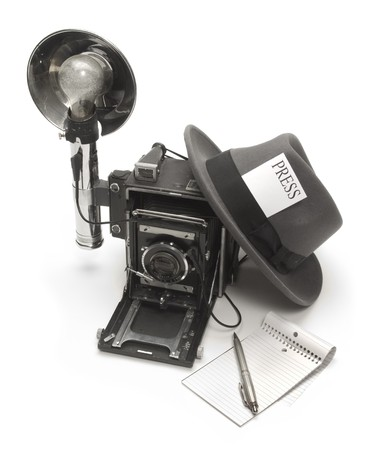 Retro photo journalist camera, fedora hat with a press pass in the headband, and ballpoint pen with notepad Banque d'images