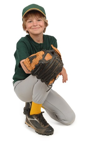 Boy in a Little League baseball uniform, posing on a white background